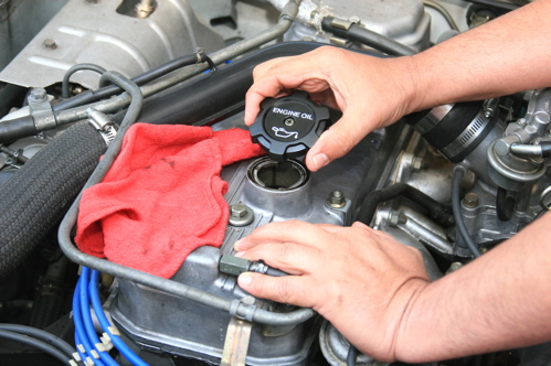 To add engine oil, find and remove the oil filler cap. Placing the cap in the rag keeps oil off the engine and the exhaust manifold.