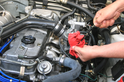 Park the car on level ground, and set the emergency brake. Open and prop up the hood, then locate the oil dipstick. Pinch a rag around the dipstick as you draw it out of the engine to remove and catch any oil.